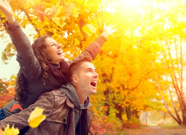 Happy Couple in Autumn Park. Fall. Family Having Fun Outdoors